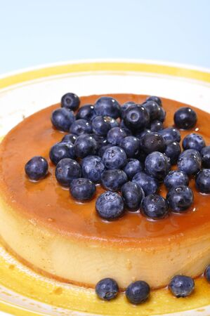flan: Vertical shot of delicious flan cheesecake topped with fresh blueberries on blue background with copy space Stock Photo