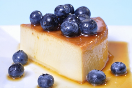 flan: Horizontal shot of delicious slice of flan cheesecake topped with fresh blueberries on blue background Stock Photo