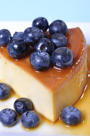 flan: Vertical shot of delicious slice of flan cheesecake topped with fresh blueberries on blue background Stock Photo