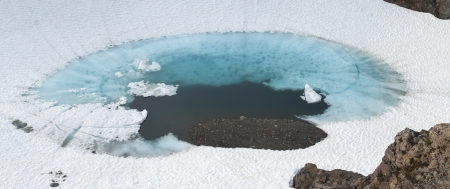 glacial: Beautiful panoramic of deep blue glacial pool surrounded by white snow on Bear Mountain in Alaska Stock Photo