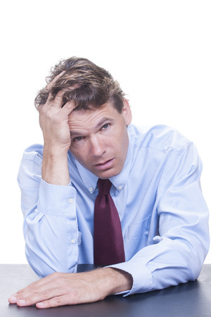 Frustrated white male office worker leans his head into his hand as he slouches at his desk fully exhausted and defeated on white background Stock Photo - 22613705