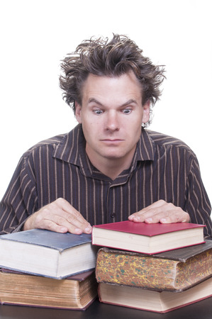 messy hair: Young male Caucasian student with wild hair stares down at pile of books he must read