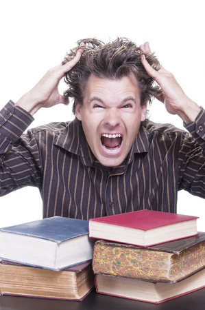 reacts: Young male Caucasian student reacts shockingly pulling out his hair with pile of academic books before him on white background
