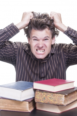 Young stressed male Caucasian student freaks out pulling hair with pile of academic books on desk on white background photo