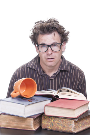 Exhausted caffeined-out male Caucasian student looks with blank stare while spilled coffee and books lie on desk on white background Banco de Imagens
