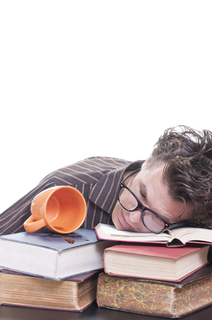 Young male Caucasian student falls asleep on books next to spilled cup of coffee on white background with copy text space