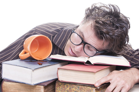 Exhausted young male Caucasian student with glasses asleep on pile of books next to spilled cup of coffee on white background with copy text space