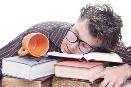 Uitgeput jonge mannelijke Kaukasische student met een bril in slaap op stapel boeken naast gemorst kopje koffie op een witte achtergrond met kopie ruimte voor tekst