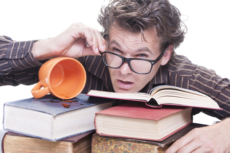 Exhausted young male Caucasian student adjusts his glasses when trying to wake up and study on pile of books with spilled cup of coffee on white background photo