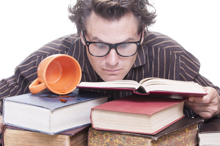 Young wide-eyed studious male Caucasian student studies intensely as he buries his eyes into pile of books next to spilled cup of coffee on white background