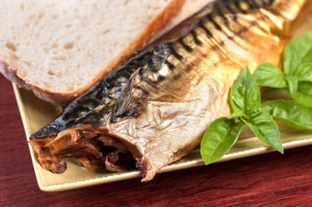Closeup of smoked fish with fresh basil and sourdough bread on sqaure plate and table