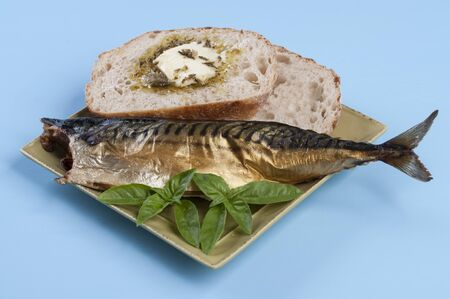 Plate of smoked fish, buttered sourdough bread, and basil on blue table