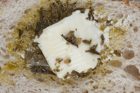 Macro closeup of soft butter and herbs on slice of sourdough bread Stock fotó