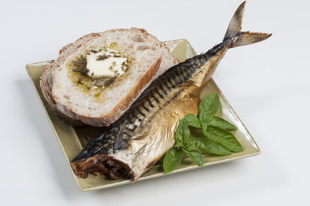 Plate of smoked fish, buttered sourdough bread, and basil on white Stok Fotoğraf