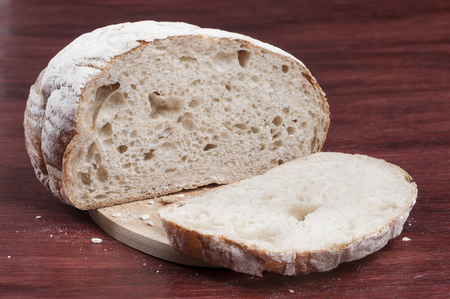 Closeup of homemade loaf of sliced sourdough bread on cutting board and wood table Stok Fotoğraf