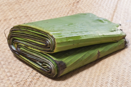 Bundle of fresh green banana leaves for cooking on woven palm mat