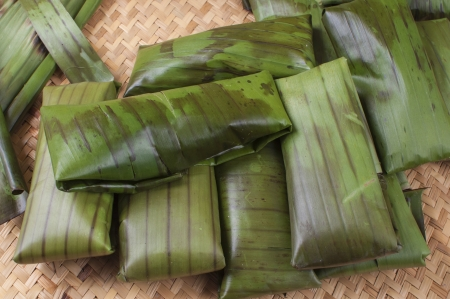 Pile of tamales freshly wrapped in banana leaves on palm woven mat prior to cooking