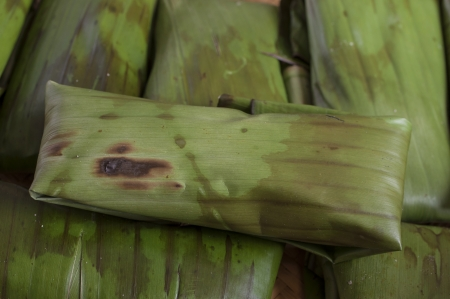 prior: Closeup of pile of tamales freshly wrapped in banana leaves prior to cooking