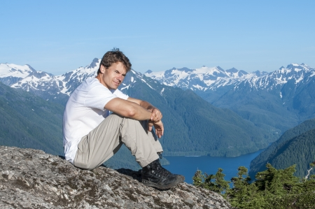 overlook: Caucasian man sits on rock on mountain peak overlooking beautiful southeast Alaska landscape including Silver Bay and mountains of Baranof Island on clear summer day
