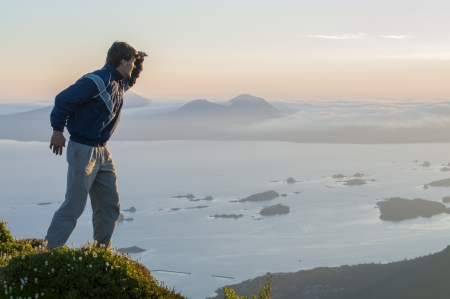 Caucasian male hiker on top of mountain looks out over Sitka Sound during summer sunset on Baranof Island in southeast Alaska photo