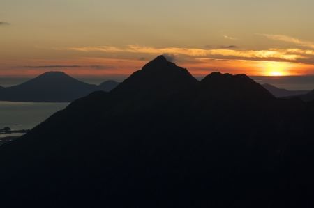 Silhouetted peak of Mount Verstovia with volcano Mount Edgecumbe in background near Sitka, Alaska during magnificent summer sunset Stock Photo - 23415186