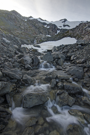 Clear mountain stream forms from summer snow melt from the rugged rocky peak of Bear Mountain on Baranof Island in southeast Alaska Stock Photo - 23415188