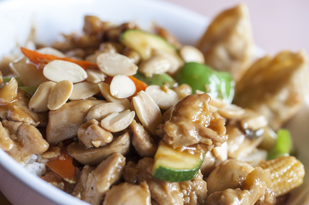 Macro closeup of bowl of Chinese almond chicken with vegetables and rice Stock Photo