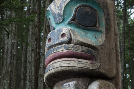 tlingit: Closeup of face of wooden Tlingit totem pole in dense pine forest in Sitka, Alaska Stock Photo