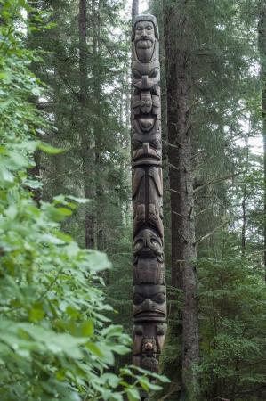 the totem pole: Tall wooden cedar Tlingit totem pole in pine forest in Sitka, Alaska Stock Photo
