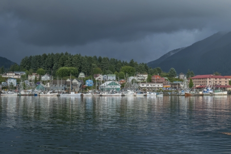 ANB Harbor and boats  with reflections and dark green pine forest in background on cloudy summer day in Sitka, Alaska Stock Photo