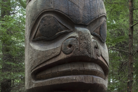 the totem pole: Closeup of face on wooden cedar Tlingit totem pole in pine forest in Sitka, Alaska Stock Photo