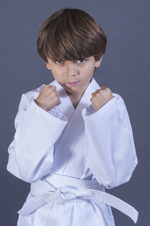 eight years old: Young handsome Caucasian boy poses in karate uniform with white belt on grey background Stock Photo