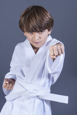 Young handsome Caucasian boy performs punch in karate uniform with white belt on grey background Reklamní fotografie