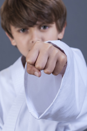 eight years old: Closeup focused on fist of young boy in karate uniform performing a punch
