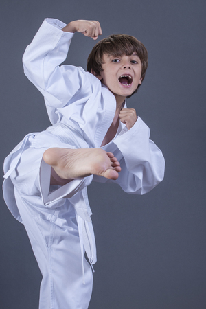 eight years old: Young handsome Caucasian boy performs side kick in karate uniform with white belt on grey background
