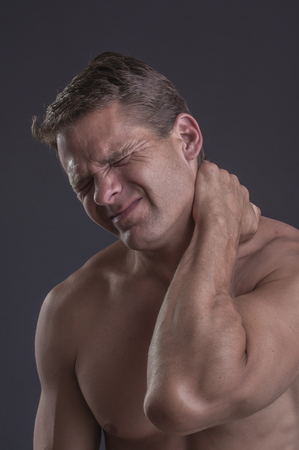 excruciating: Athletic muscular shirtless man massages sore neck with hand to ease intense pain on grey background Stock Photo