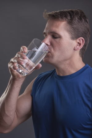 Handsome muscular male athlete drinks a clear tall glass of pure water on grey background