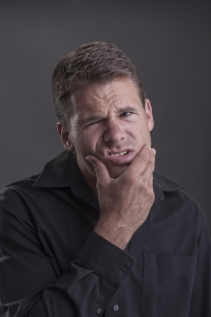Caucasian man wearing black shirt holds his lower jaw and contorts his face in agony on grey background Stock Photo