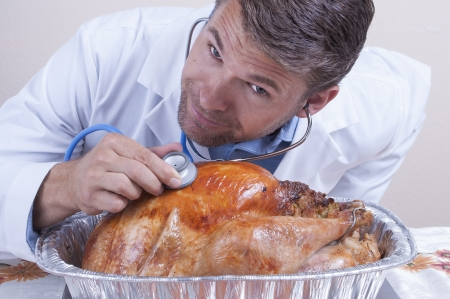 funny turkey: Funny closeup of smiling male Caucasian medical doctor listening with stethoscope for heartbeat of baked Thanksgiving turkey