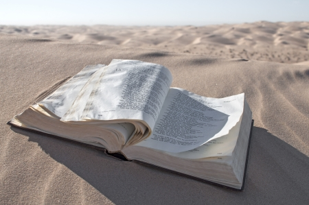 Oude Christelijke Bijbel open ligt in de woestijn duinen met pagina klapperen in de wind Stockfoto