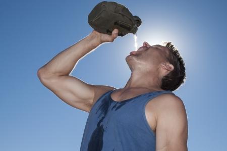 transpiration: Tr�s soif homme de race blanche de sport verse de l'eau dans la bouche de cantine militaire sur chaude journ�e ensoleill�e