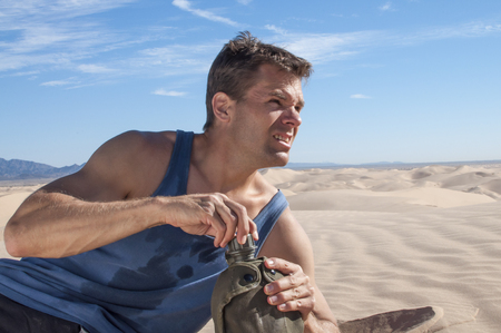Athletic thirsty Caucasian male hiker lies down in sand dunes to open water canteen in hot dry barren desert Stock Photo
