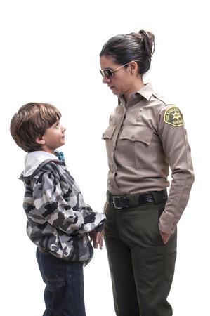 Jonge elementaire jongen wordt geconfronteerd door vrouwelijke sheriff afgevaardigde op een witte achtergrond Stockfoto