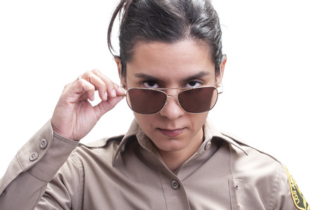 deputy: Pretty Hispanic female sheriff deputy dips sunglasses revealing bold penetrating eyes on white background