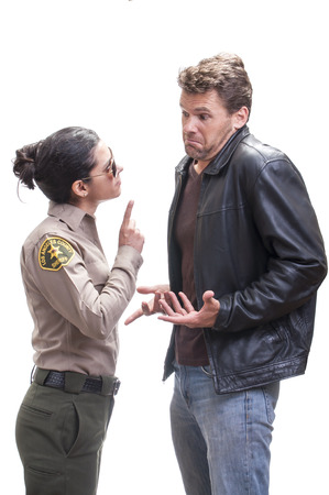 warns: Petite young female Hispanic sheriff deputy questions and warns tall male Caucasian suspect on white background Stock Photo