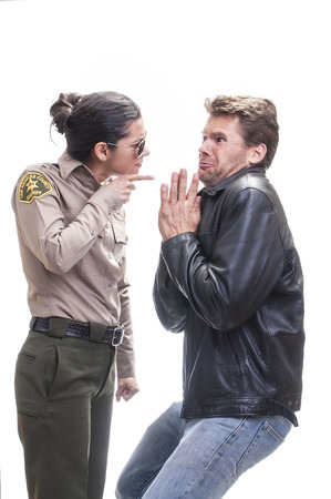 deputy sheriff: Frightened Caucasian law breaker begs for mercy and receives warning from young bold female sheriff deputy on white background