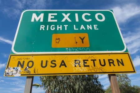 warns: SAN YSIDRO, USA - NOVEMBER 27, 2013  Stickers and vandalism cover the traffic sign on the corner of Camino de la Plaza and Interstate 5 on-ramp in San Ysidro that both directs and warns drivers that the right lane leads only to Mexico