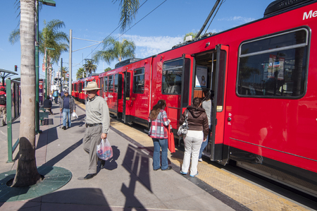 southernmost: SAN YSIDRO, USA - NOVEMBER 27, 2013  Passengers board the San Diego blue line trolley at the southernmost station stop at the US - Mexico border crossing in San Ysidro on November 27, 2013   The blue line runs along Interstate 5 making numerous stops betw