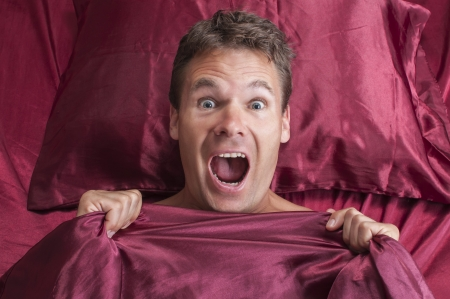 Closeup of terrified Caucasian man reacting to nightmare and screaming under red bed sheets
