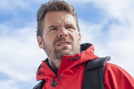 strenuous: Closeup of determined bearded Caucasian man hiking with intense strenuous expression wearing red jacket and sky in background